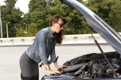 Confused молодая женщина смотря сломанный вниз с двигателя автомобиля на улице Стоковая Фотография