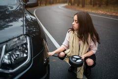 Confused молодая женщина смотря сломанный вниз с ремонта автомобиля двигателя автомобиля на улице Стоковое Изображение