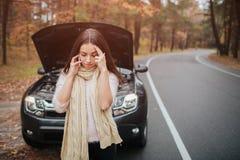 Confused молодая женщина смотря сломанный вниз с ремонта автомобиля двигателя автомобиля на улице Стоковые Фото