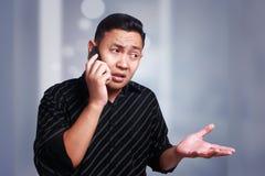 Confused молодой человек говоря на его телефоне стоковое изображение