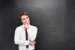 Confused молодой человек на предпосылке доски стоковое изображение