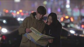 Confused пары студентов проверяя карту для того чтобы найти правильное направление, путешествуют за рубежом видеоматериал