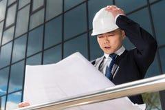 Confused профессиональный архитектор в трудной шляпе смотря светокопию Стоковое Изображение