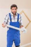Confused рабочий-строитель держа уровень духа стоковое фото rf