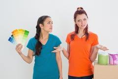 Confused друзья выбирая цвет для красить комнату Стоковые Фото