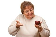 Confused старшая женщина держа Яблоко и витамины Стоковые Фото