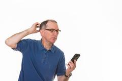 Confused старший человек с сотовым телефоном стоковые изображения rf