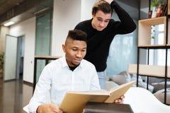 2 confused студента в библиотеке уча материал образования Стоковое Изображение RF
