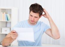 Confused человек смотря бумагу стоковые фотографии rf