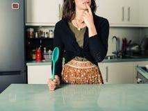 Confused женщина с ложкой в кухне стоковое фото rf
