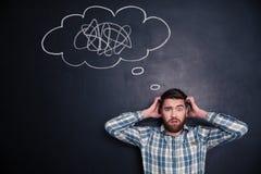 Confused человек думая о проблеме с черной доской за им Стоковое Изображение RF