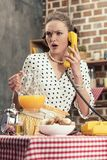 confused adult housewife talking by vintage wired phone royalty free stock images