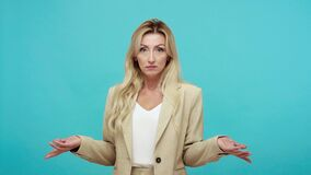 Confused adult woman in business jacket shrugging shoulders, puzzled by information, uncertain