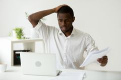 Confused african-american businessman having problem with comput. Confused african-american businessman having problem with documents looking at laptop at work Stock Photography