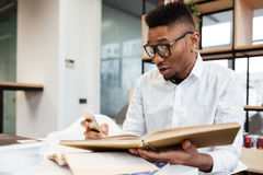 Confused african student in library learning education material. Photo of confused african student wearing eyeglasses in library learning education material with Stock Photography