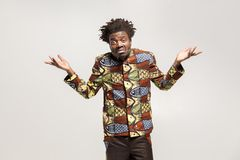 Confused afro man puzzled and say don`t know, maybe. Indoor, isolated on gray background royalty free stock photos