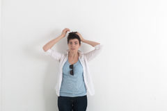 The confused amusing funny young woman with messy tousled short dark hair holding hands to her head on light grey. Background Stock Images