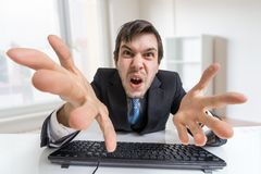 Confused angry businessman is working with computer in office Royalty Free Stock Images