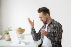 Confused angry man frustrated by online problem, hate stuck lapt. Confused angry young man frustrated by online problem, casual businessman looking at stuck Royalty Free Stock Photo