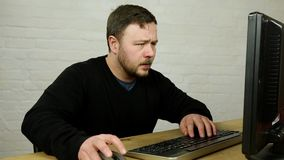 Confused angry man typing on keyboard in front of slow or broken computer stock footage