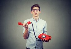 Confused annoyed teenager man with old fashioned telephone. Confused teenager man with old fashioned red telephone on gray background Royalty Free Stock Photo