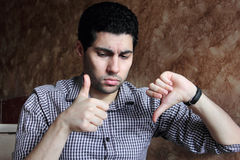 Confused arab egyptian businessman with thump down and up Royalty Free Stock Photography