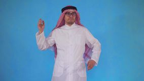 Confused arab man stands on a blue background. Confused arab man with glasses stands on a blue background stock video footage