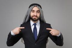 Confused arabian muslim businessman in keffiyeh kafiya ring igal agal classic black suit shirt isolated on gray