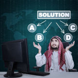 Confused Arabic businessman choosing a solution Stock Photo