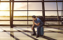 Confused asian tourist sitting on suitcase waiting departure Royalty Free Stock Images