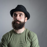 Confused bearded man wearing black hat looking away Stock Photography