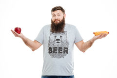Confused bearded young man between healthy and unhealthy food Royalty Free Stock Image