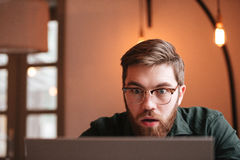 Confused bearded young man using laptop computer. royalty free stock photo