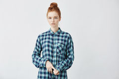 Confused beautiful redhead girl with big bun looking at camera. Beautiful redhead girl in coloured checked shirt looking straight at camera. Isolated on white Royalty Free Stock Image