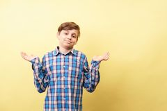 Confused bewildered clueless boy lifting hands. In dismay over yellow background, advertisement, banner or poster template, emotion facial expression, people stock images