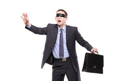Confused blindfold businessman with briefcase. Isolated on white background stock photos