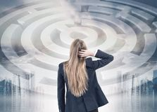 Confused blonde businesswoman, maze toned. Rear view of a confuesed blonde businesswoman scratching her head and looking at a labyrinth sketch, toned image Royalty Free Stock Image