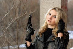 Confused blonde girl with a gun Stock Photo