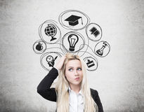 Confused blonde woman and education icons. Portrait of a confused blond woman standing near a concrete wall with education icons and scratching her head Stock Photos