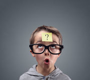 Confused boy thinking with question mark. On sticky note on forehead royalty free stock photo
