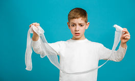 Confused boy in white clothes holding medical bandage Stock Image