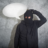 Confused burglar with speech balloon. Concept, thief with balaclava caught confused and without idea in front of the grunge concrete wall royalty free stock photography