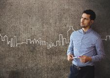 Confused business man standing against grey wall background with city icons Royalty Free Stock Image