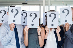 Uncertainty and problem solving. Confused business team holding a question mark sign in front of his face in office. Uncertainty and problem solving concept Stock Photography