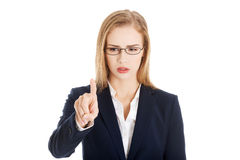 Confused business woman in eyeglasses is looking at her finger. Stock Images