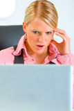 Confused business woman looking on laptop. Portrait of confused modern business woman looking on laptop Royalty Free Stock Photos
