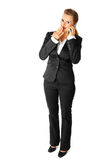 Confused business woman talking on mobile phone Royalty Free Stock Image