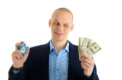 Confused Businessman with alarm clock and stack of cash in hand. Time is money concept. Confused Businessman with alarm clock and stack of cash in hand. Time is Royalty Free Stock Photos
