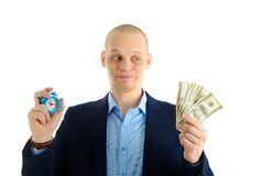Confused Businessman with alarm clock and stack of cash in hand. Time is money concept. Confused Businessman with alarm clock and stack of cash in hand. Time is Stock Images