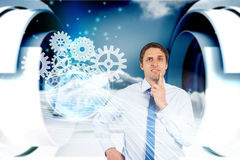 Confused businessman with cogs and wheels graphics Royalty Free Stock Photography